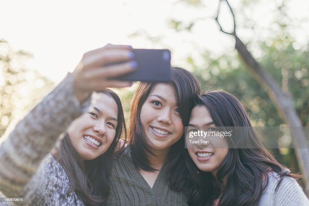 Three teenage girls taking photos of themselves : Stock Photo