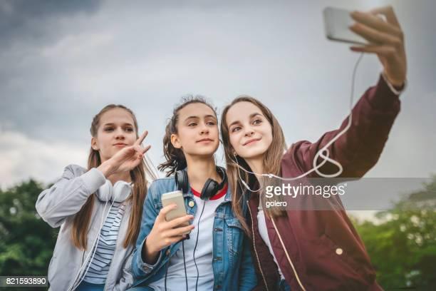 three teenage girls taking selfie outdoors