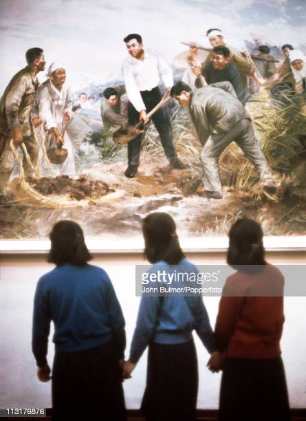 Three teenage girls viewing a painting in a museum in North Korea February 1973