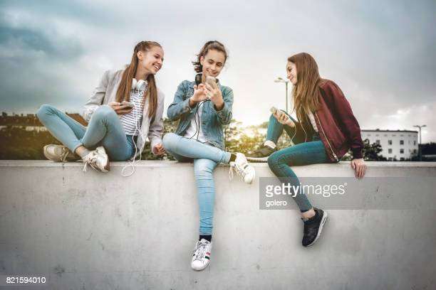 three teenage girls with smartphones on concrete wall