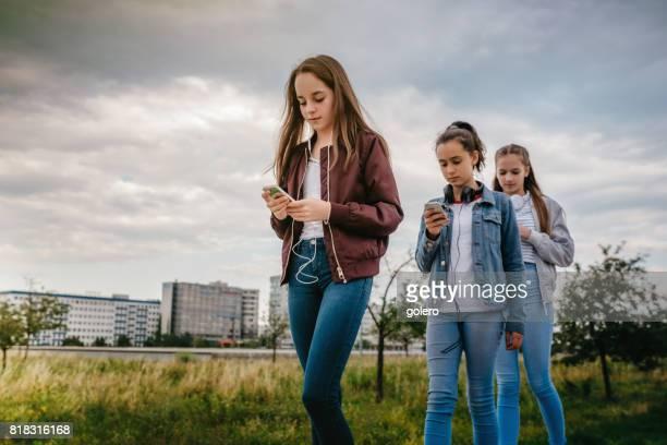 three teenage girls with smartphones walking