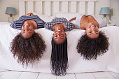 Three Teenage Sisters With Long Hair Lying On Bed At Home