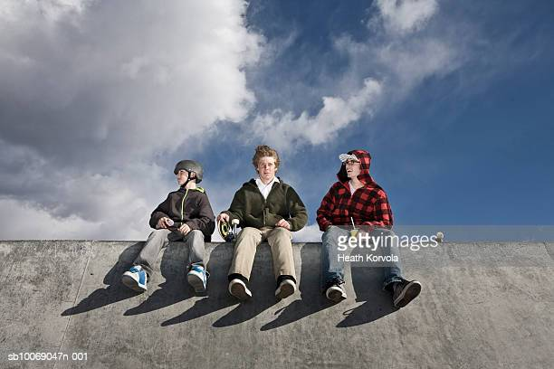 Three teenage (11-21) skaters sitting on edge of skate park, low angle view