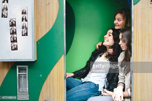 three teenager girls together in photo booth making faces