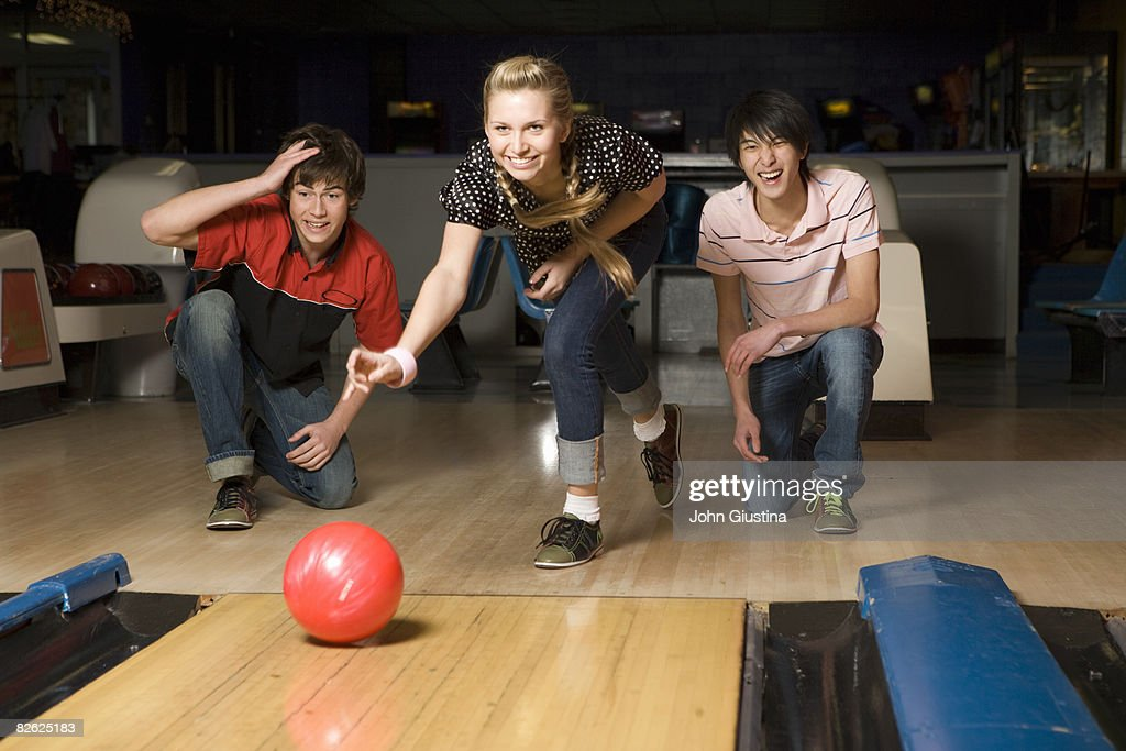 Three teenagers (15-17) bowling.
