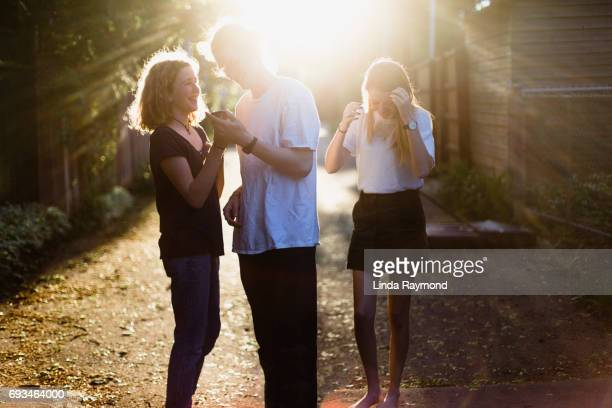 Three teenagers having fun with a cellphone in an alley at sunset