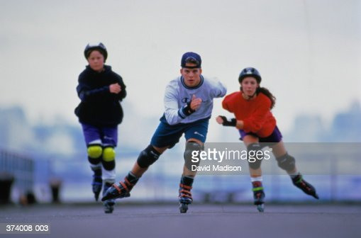 Three teenagers (16-18) in-line skating, front view