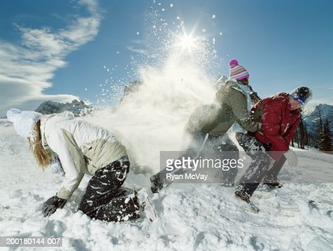 Tres adolescentes (15 a 17) roughhousing en la nieve, vista lateral : Foto de stock