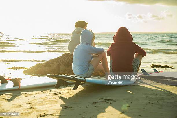 Three teenagers sitting on the beach watching sunset