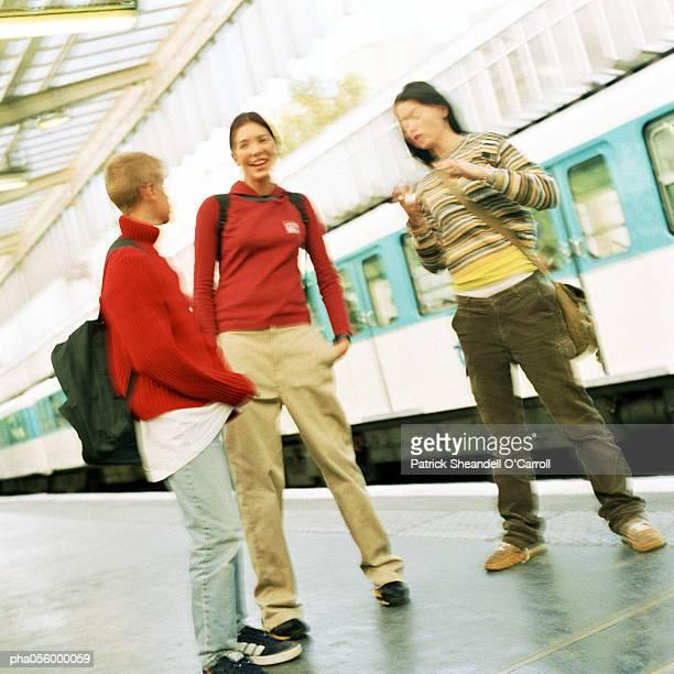 Three teenagers standing on subway platform, blurred