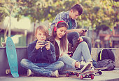 Group of ordinary teenagers in casual relaxing with mobile phones outdoor. Focus on girl