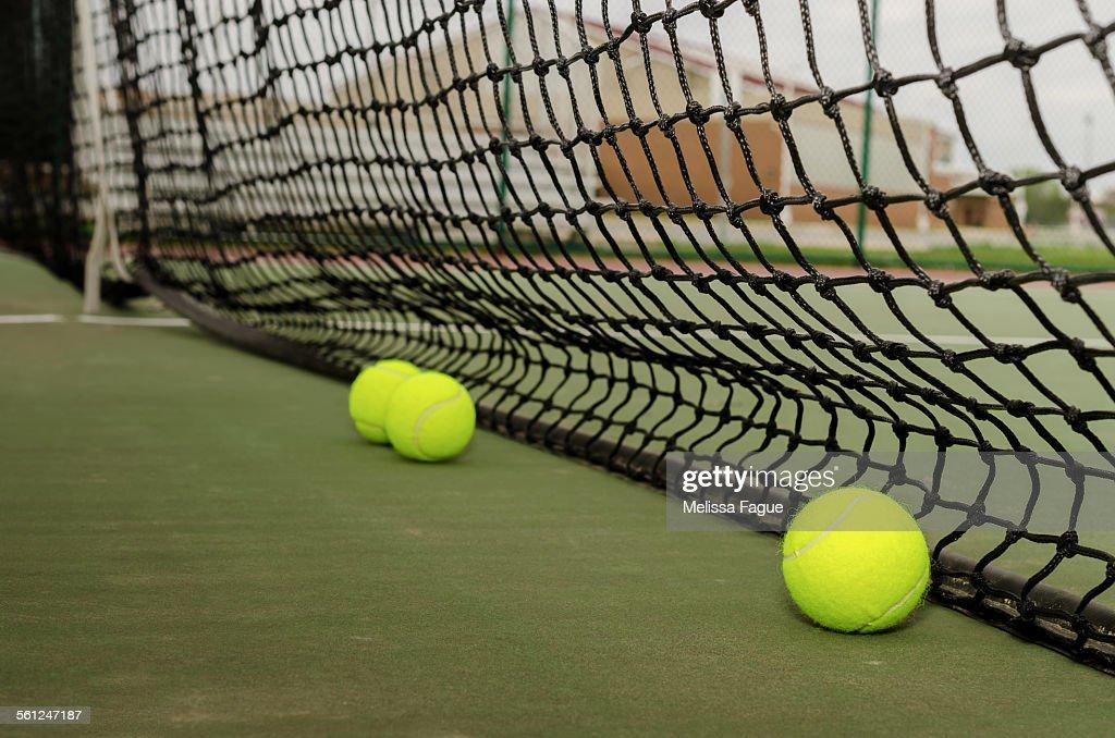 Three tennis balls near net