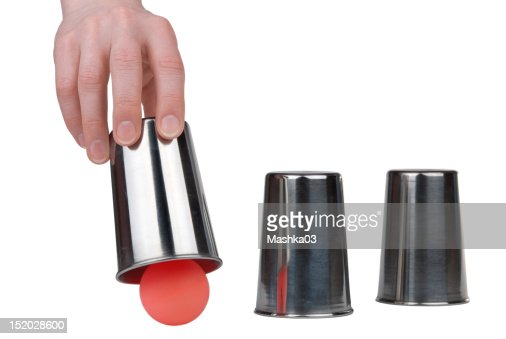 Three thimbles with a ball under one of them : Stock Photo