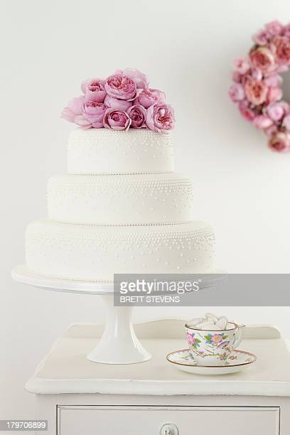 Three tiered wedding cake with pink floral arrangement and cup and saucer
