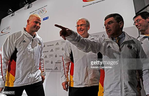 Three time Olympic gold medalist German bobsleder André Lange looks at Dr Thomas Bach a vicepresident and member of the executive board of the...