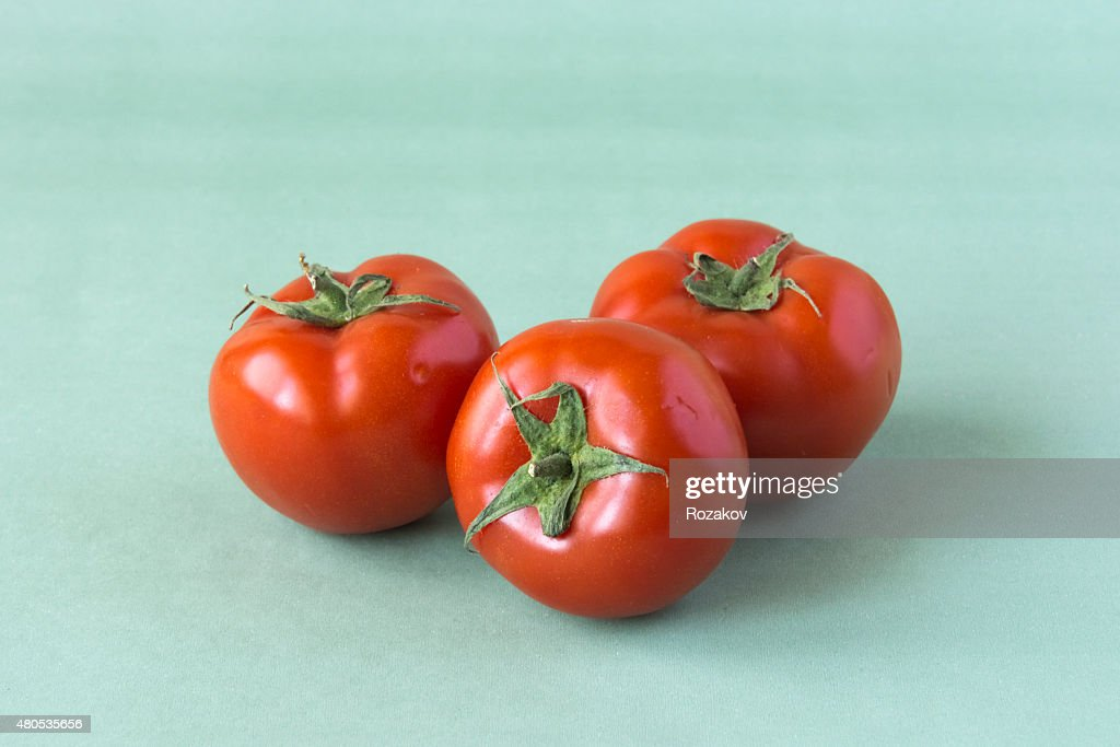 Three tomatoes on a green background : Stock Photo