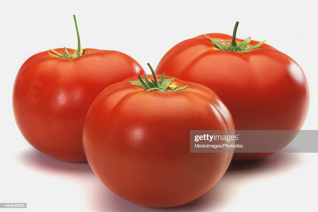 Three tomatoes on counter, close-up : Stock Photo