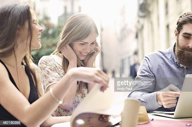 Three tourist friends enjoying a break at sidewalk cafe, Valencia, Spain