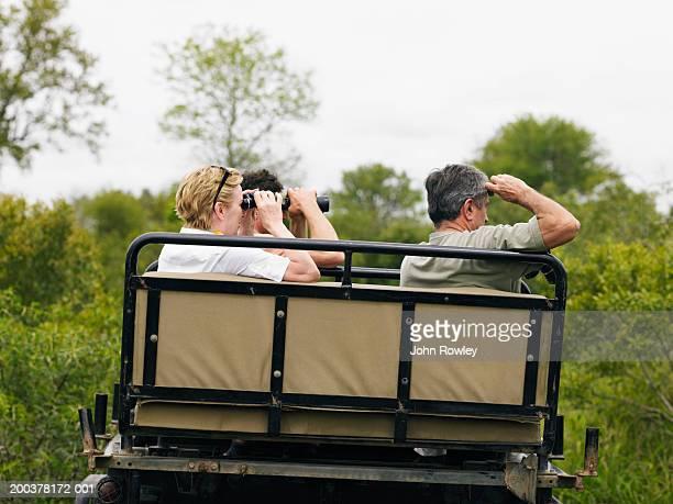 Trois touristes sur safari assis en 4 x 4 à l'aide de jumelles