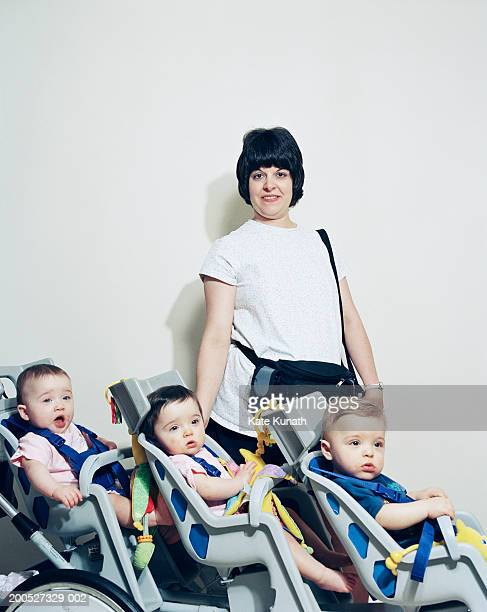 Three triplets (6-12 months) with mother in pushchair, side view