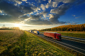 Three trucks driving on a highway in autumn landscape at sunset with dramatic clouds