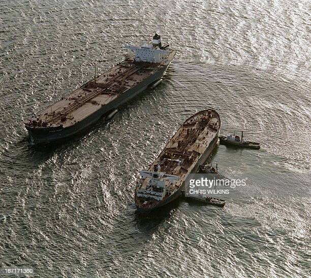 Three tugboats push the oil tanker Exxon San Francisco into place beside the crippled tanker Exxon Valdez in Prince William Sound 30 March 1989 to...