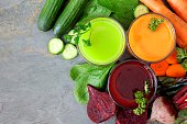 Three glasses of healthy vegetable juice with scattered ingredients, above view over a slate background
