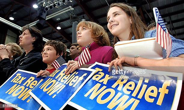 Three unidentified young girls watch US President George W Bush address a rally at Joe Foss Field National Guard Hangar on his tax cut plan 09 March...