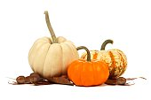 Group of three unique autumn pumpkins with leaves over a white background