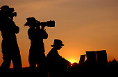 Three US Air Force (USAF) Visual Information professionals: a videographer (left), a still photographer (center), and a graphics specialist (right), are all highlighted by the setting sun.