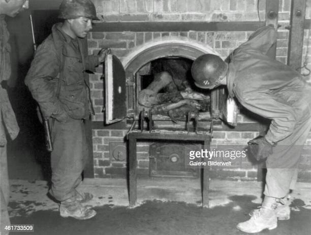Three US soldiers look at bodies stuffed into an oven in a crematorium April 1945 Photo taken in an unidentified concentration camp at the time of...