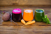 three vegetable juice in a glass cup on a wooden background