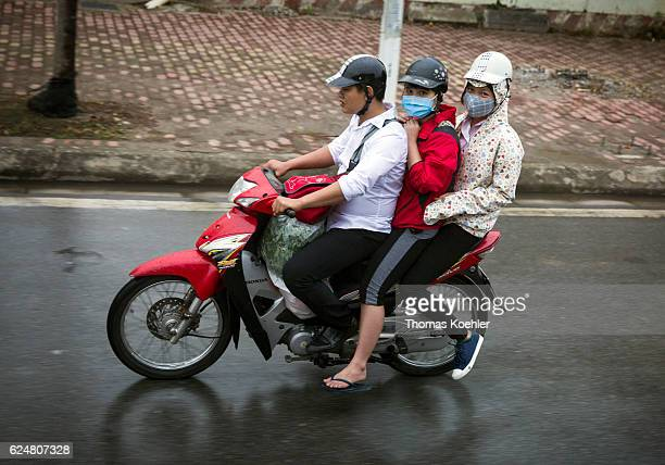Three Vietnamese people with respiratory masks driving on a motorbike through the city traffic in Hanoi on October 30 2016 in Hanoi Vietnam