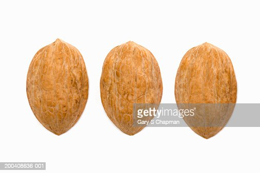 Three walnut shells on white background