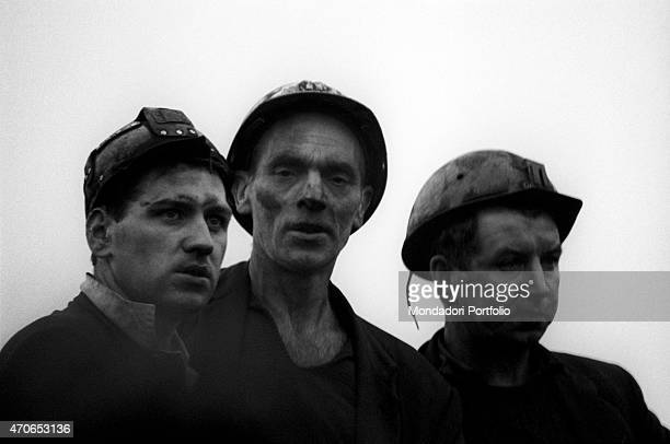 'Three Welsh miners with safety helmets on and their faces covered in mud and soot gaze at the horizon after the landslide that devastated their...