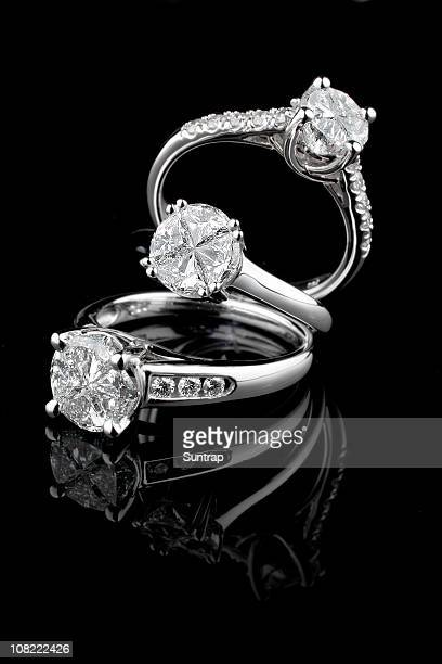 Three white gold diamond rings on black background