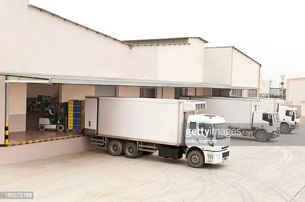 Three white trucks in front of a warehouse