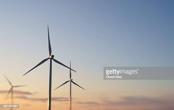 Três turbinas eólicas ao pôr do sol.