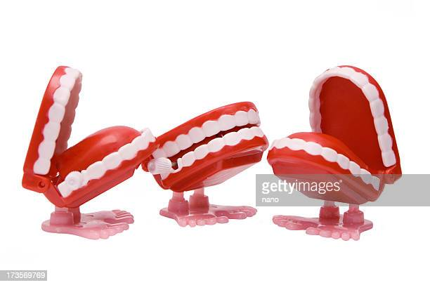 Three wind-up chattering teeth toys with feet