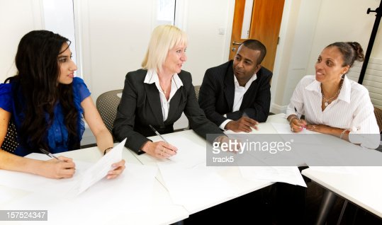 Three woman and a man attending and having a discussion at a business meeting