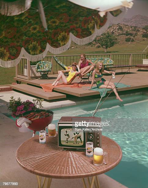Three woman in swimwear relax at a poolside while in the foreground a portable television set shows a baseball game 1967 The photo was taken as part...