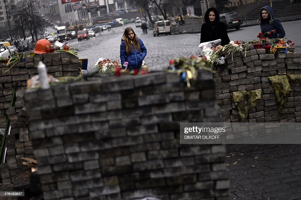 Three woman mourn near a homage to victims of the February clashes between anti-government protestors and riot police at a barricade on Independence square in central Kiev on March 3, 2014. Russia has effectively 'declared war' on Britain and the United States through its actions in Crimea, Ukraine's newly-freed opposition leader Yulia Tymoshenko warned on Monday.