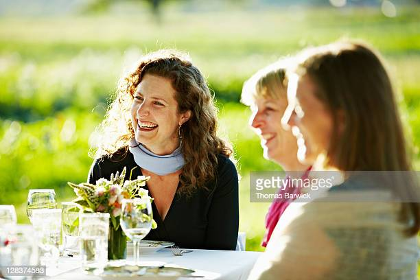 Three woman sitting at table outside smiling