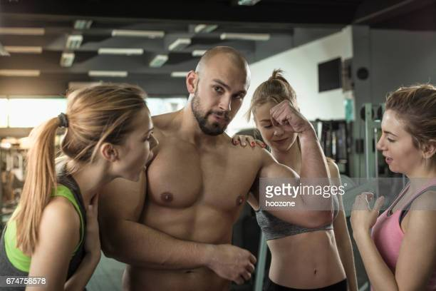Three women admiring mens big muscles at gym