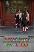 Three women and a man playing jianzi with a shuttlecock during morning exercises in Beihai Park an imperial garden to the northwest of the Forbidden...