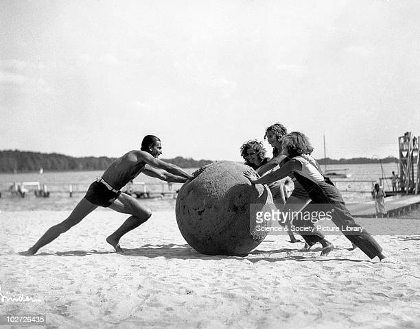 Three women and a man pushing a huge ball 1930s Three women and a man pushing a huge beach ball on a sandy beach c1930