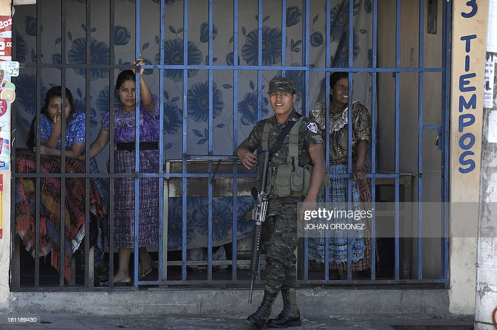 Three women and a soldier observe a crime scene from afar in downtown Guatemala City on February 9, 2013. A vehicle was attacked by unidentified gunmen while traveling toward a prison; leaving two prison guards and a woman dead, authorities stated. AFP PHOTO/Johan ORDONEZ