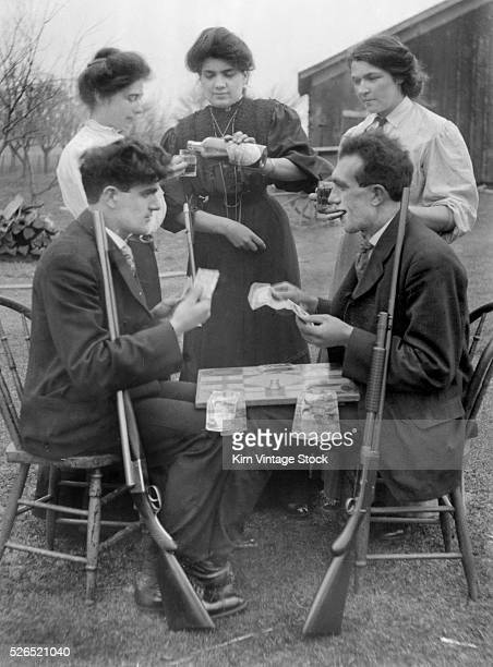 Three women and two men gamble drink alcohol smoke cigars and have weapons ready for gun play in a staged photograph at the beginning of the 20th...
