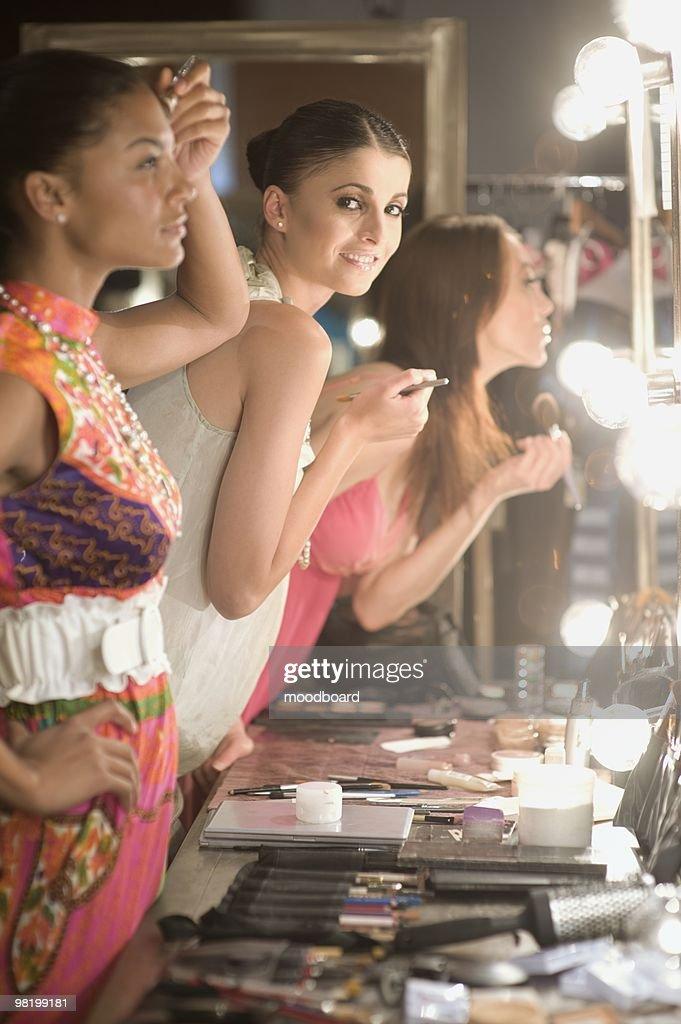 Three women apply makeup in dressing room mirror : Stock Photo