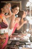 Three women apply makeup in dressing room mirror